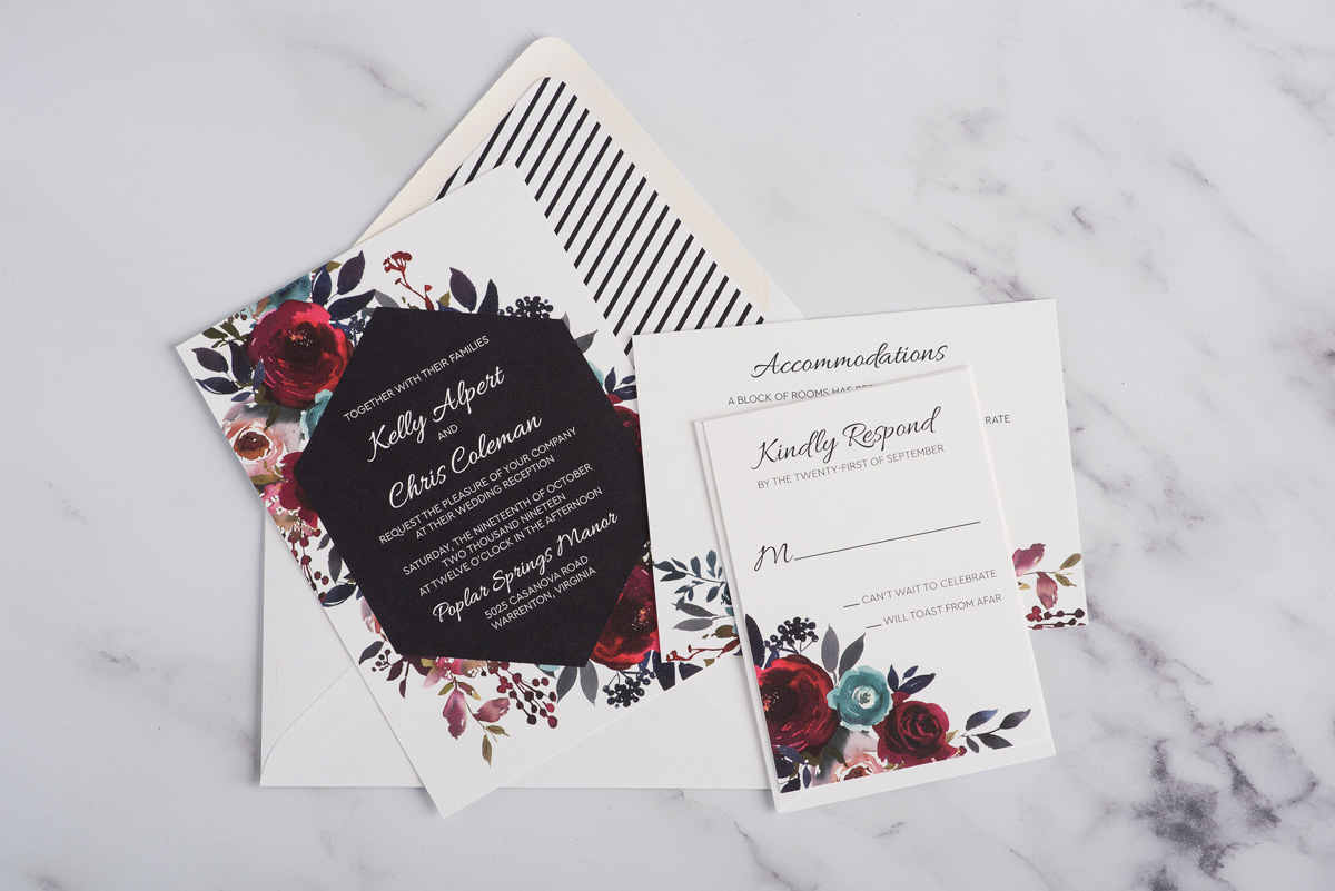 A navy hexagon frames white text and is embellished with bold burgundy floral watercolor artwork.  A striped envelope liner was an unexpected pop to tie everything together in these custom wedding invitations.