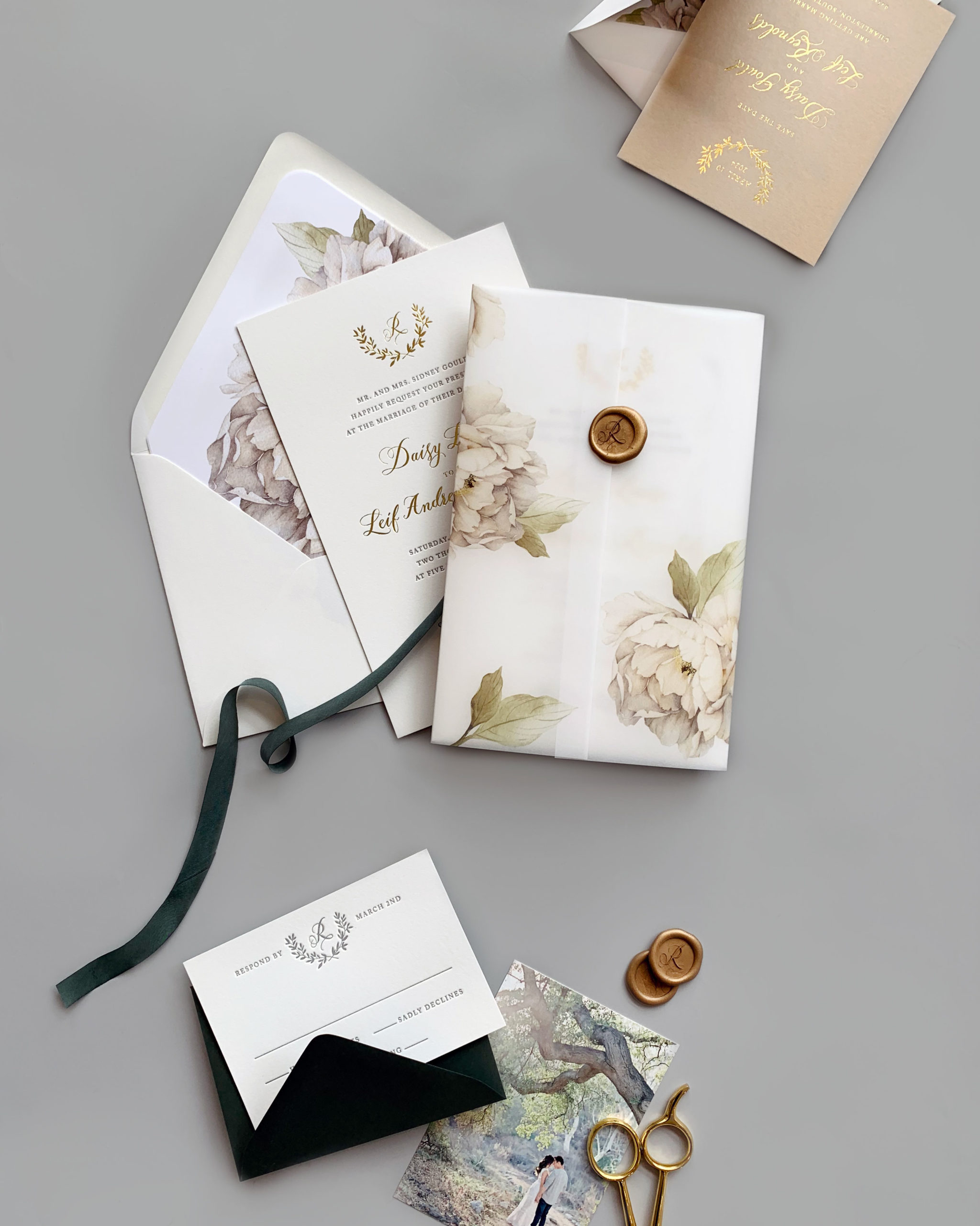A floral printed vellum gate fold surrounds a formal letterpress and foil stamped wedding invitation.  Neatly closed with a custom wax seal, these wedding invitations from Staccato are perfectly on-trend.