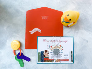 "Bright orange envelope with white ink addressing is the perfect pop to get guests' attention. This layered baby shower invitation is wrapped in string and accented with a wax seal that says ""it's a boy!"". Bright colors, a library of books, and a collection of stuffed animals all make this the perfect way to welcome the newest family member!"