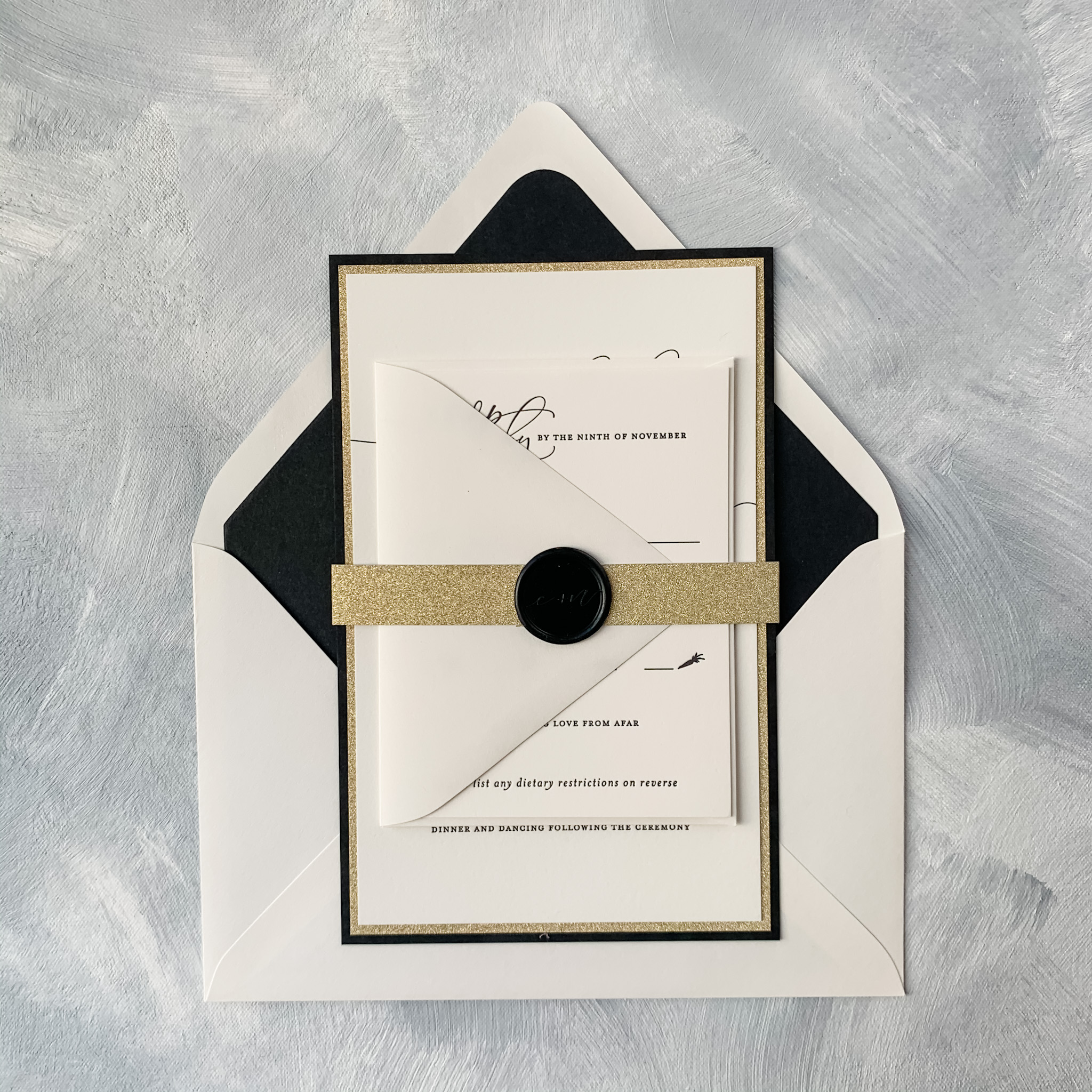 Bold and beautiful!  This modern wedding invitation by Smitten on Paper features a thin gold glitter band closed with a wax seal.  Modern letterpress is layered to both gold glitter and black accent layers, and a black envelope liner completes this dramatic look.  Luxury wedding invitations are available at Staccato in Fairfax, Virginia.
