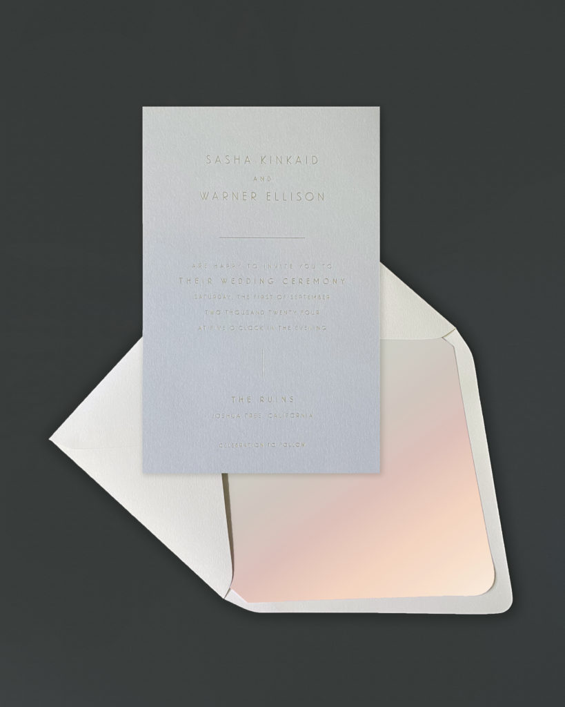 Pretty gray invitation with matte gold foil is set beautifully against a sunset color scheme watercolor envelope liner.  Shop luxury wedding invitations and stationery at Staccato in Northern Virginia.