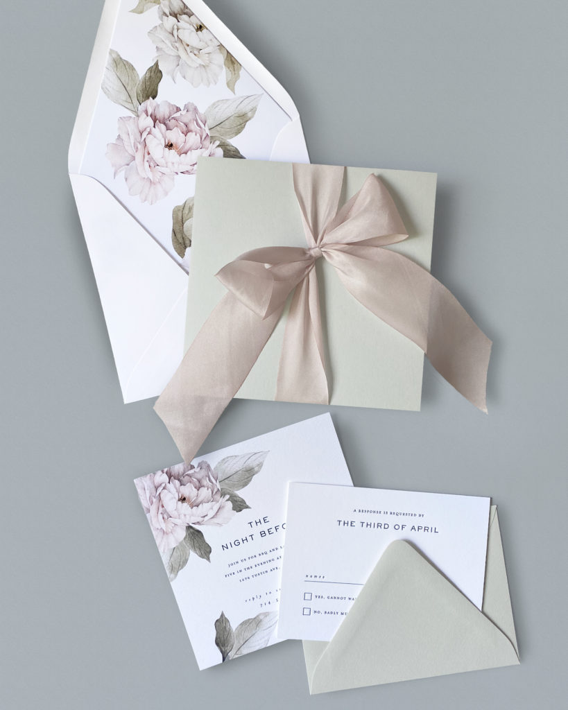 A gray square folio is closed with a wide silk ribbon housing this lovely letterpress wedding invitation featuring peony floral accents.  Luxury wedding invitations from Staccato in Northern Virginia.